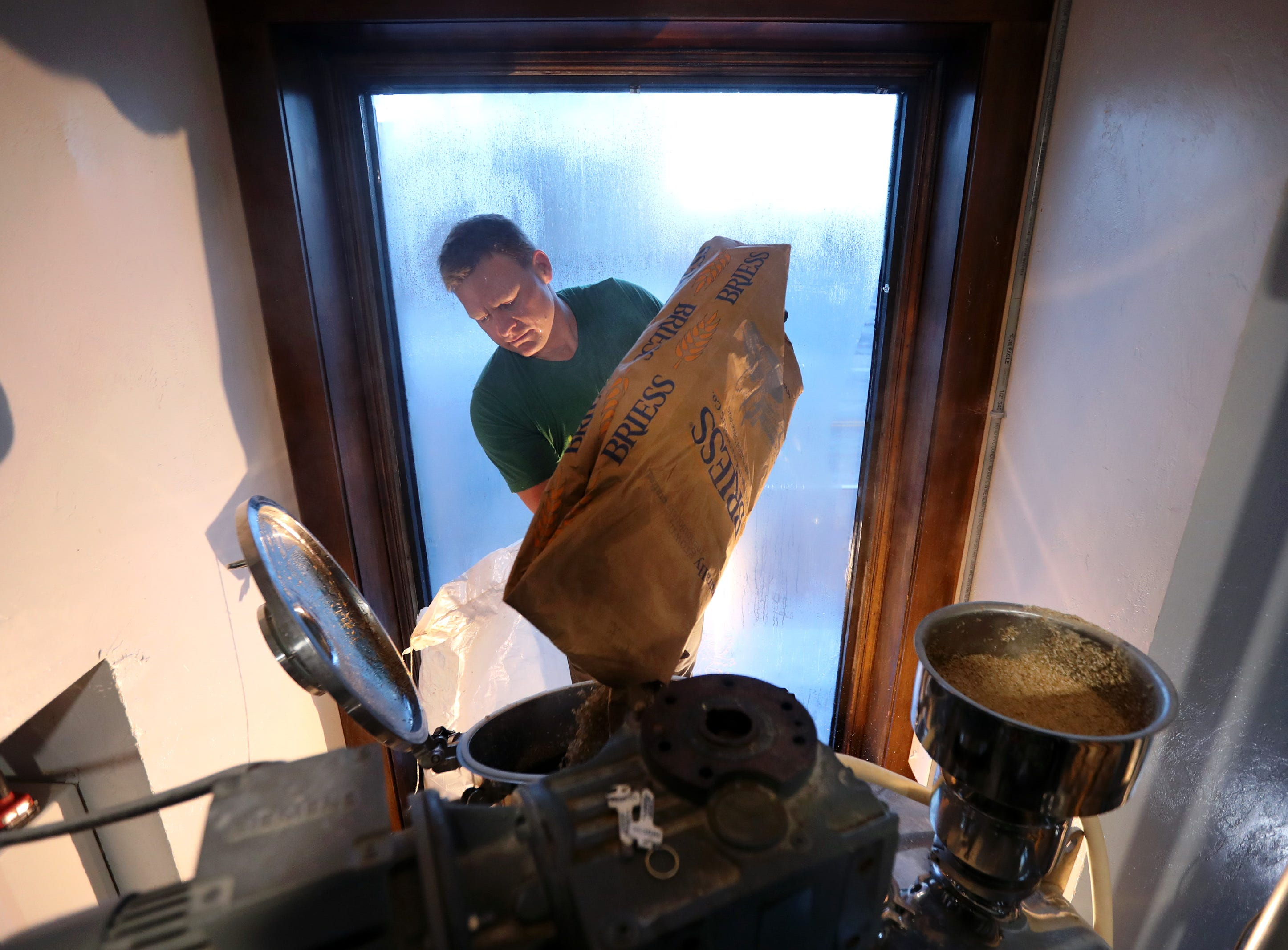 Alex Wenzel, owner and brewmaster at Lion's Tail Brewery, pours oat flakes while brewing their New England IPA Juice Cloud Thursday, Dec. 6, 2018, in Neenah, Wis.