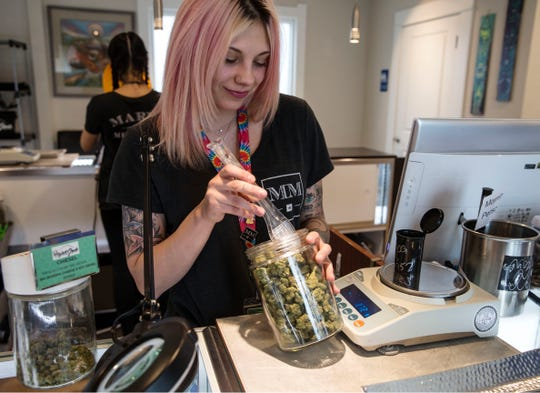 Bud tender Summer Barker measures out marijuana flower for a medical customer. Higher Grade dispensary offers fine cannabis for medicinal purposes. 