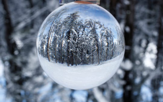 Snow covered trees at Ocean County Park in Lakewood are shown through a glass sphere Thursday morning, March 22, 2018.