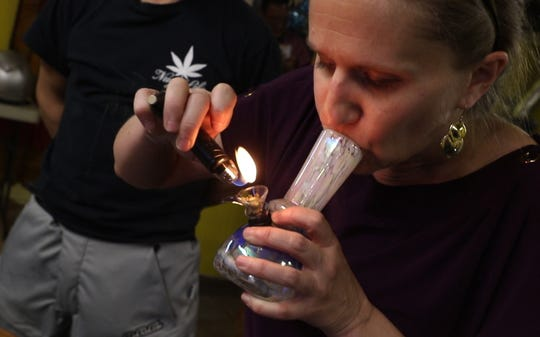 A patron of a marijuana membership lounge in Denver, Colorado, smokes cannabis.