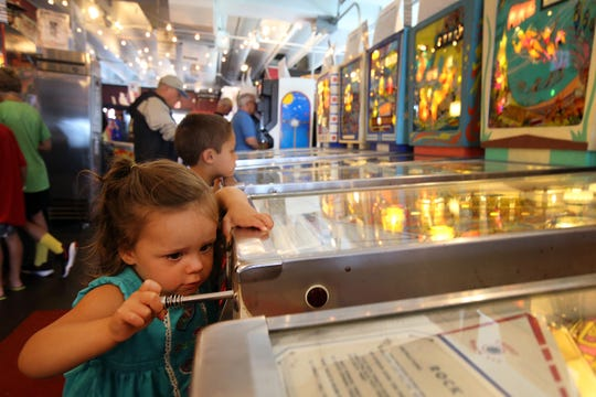 Maisie Scull, 2, of Lake Como and her brother, Fischer, 7, play pinball with their father, (not pictured) Jeff, at Silverball Museum in Asbury Park.  August 31, 2018.