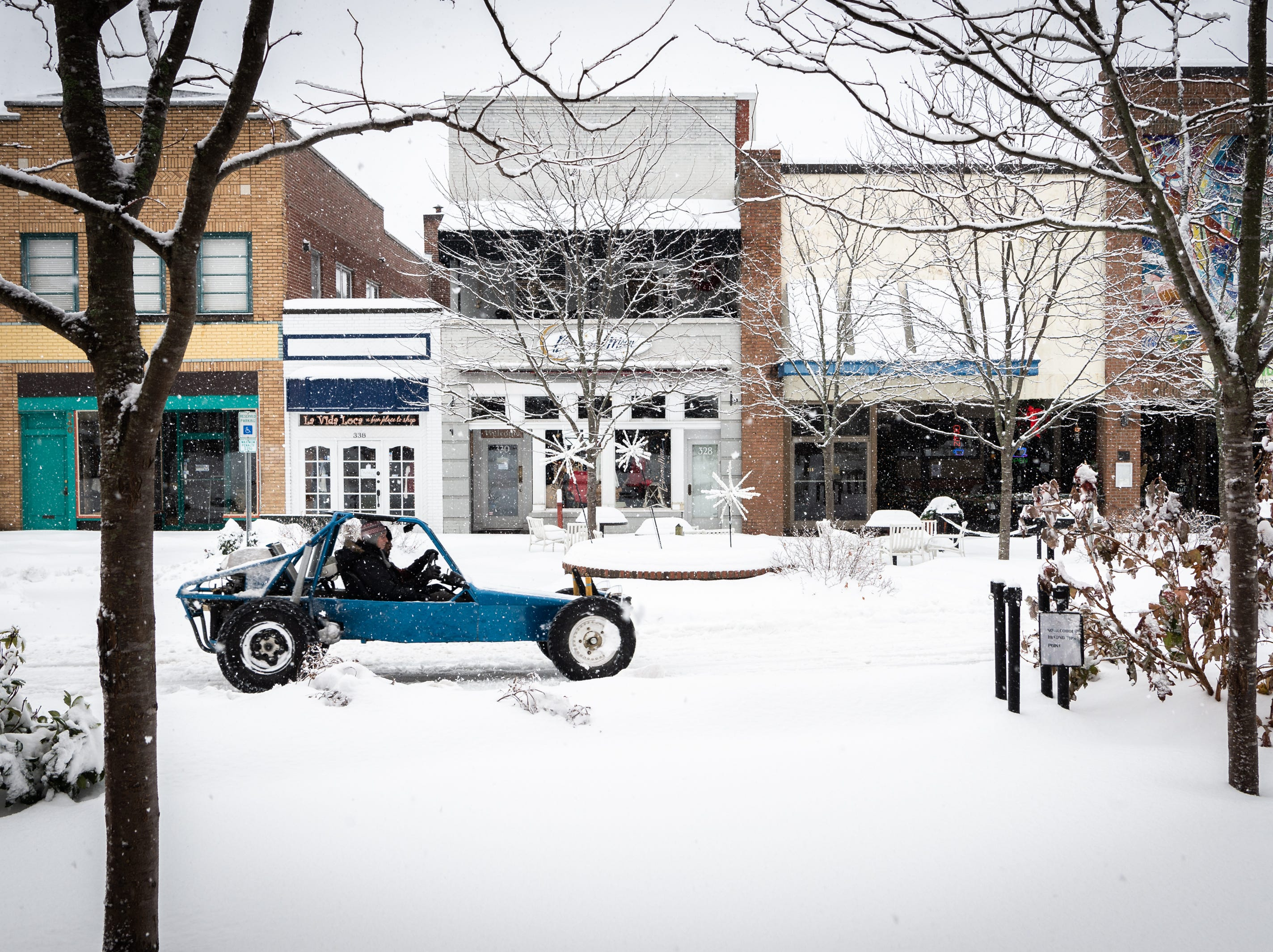 A couple in an all terrain buggy drive down Main Street in Hendersonville after a night of heavy snowfall, accumulating 10-11 inches Dec. 9, 2018. At 5 p.m there were nearly 9,600 power outages.