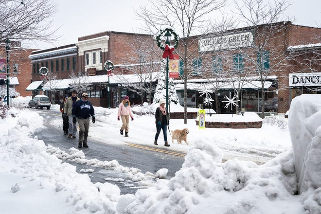 Jon Parce, Joy Coe, with her dog Mika, her daughter Addy Coe, husband Joe Coe, and daughter Margaret Torchio walk down Main Street in Hendersonville after a night of heavy snowfall, accumulating 10-11 inches Dec. 9, 2018. At 5 p.m there were nearly 9,600 power outages.