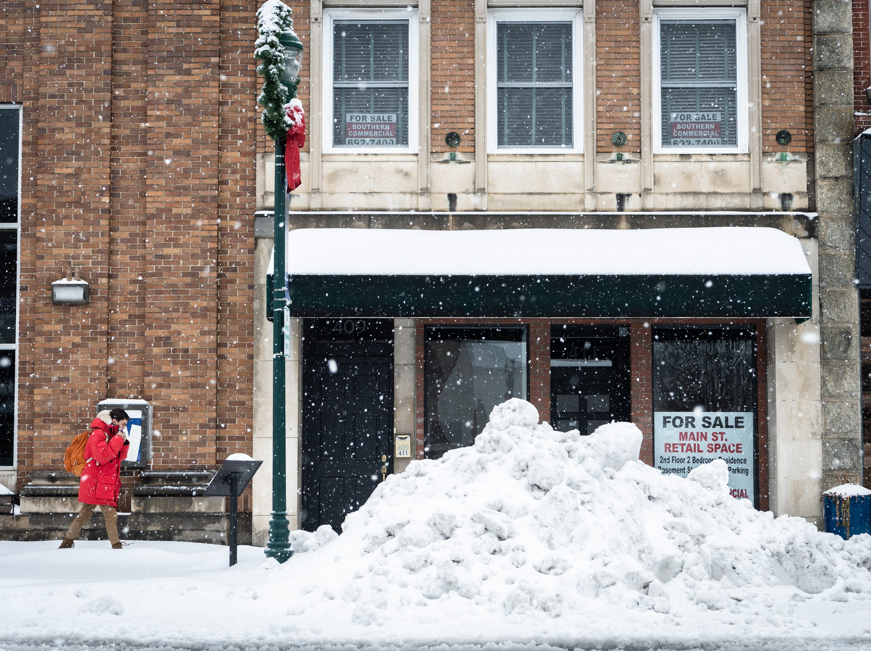 A pedestrian strolls down Main Street in Hendersonville after a night of heavy snowfall, accumulating 10-11 inches. At 5 p.m there were nearly 9,600 power outages.