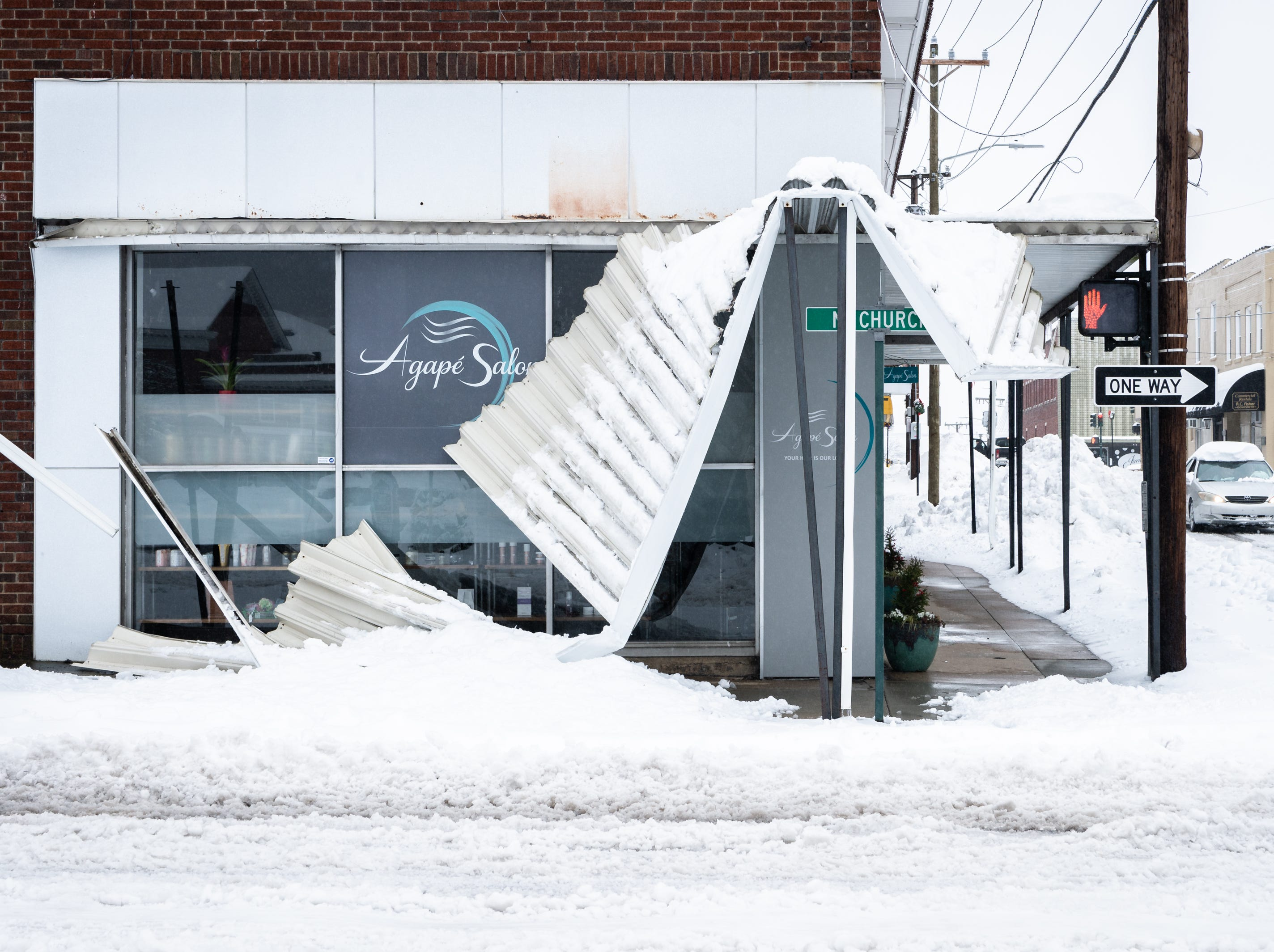 The metal awning of a business on Church Street in Hendersonville collapsed under the weight of snow after a night of heavy snowfall, accumulating 10-11 inches Dec. 9, 2018. At 5 p.m there were nearly 9,600 power outages.