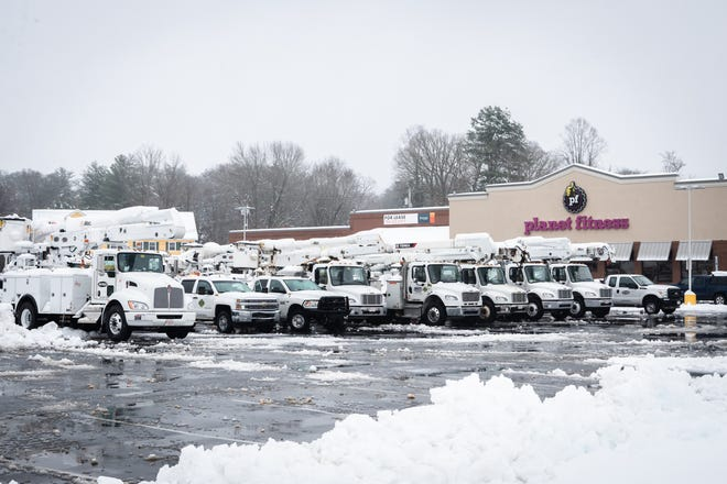 Utility company trucks sit in a Planet Fitness parking lot on Spartanburg Highway in Hendersonville after a night of heavy snowfall, accumulating 10-11 inches Dec. 9, 2018. At 5 p.m there were nearly 9,600 power outages.