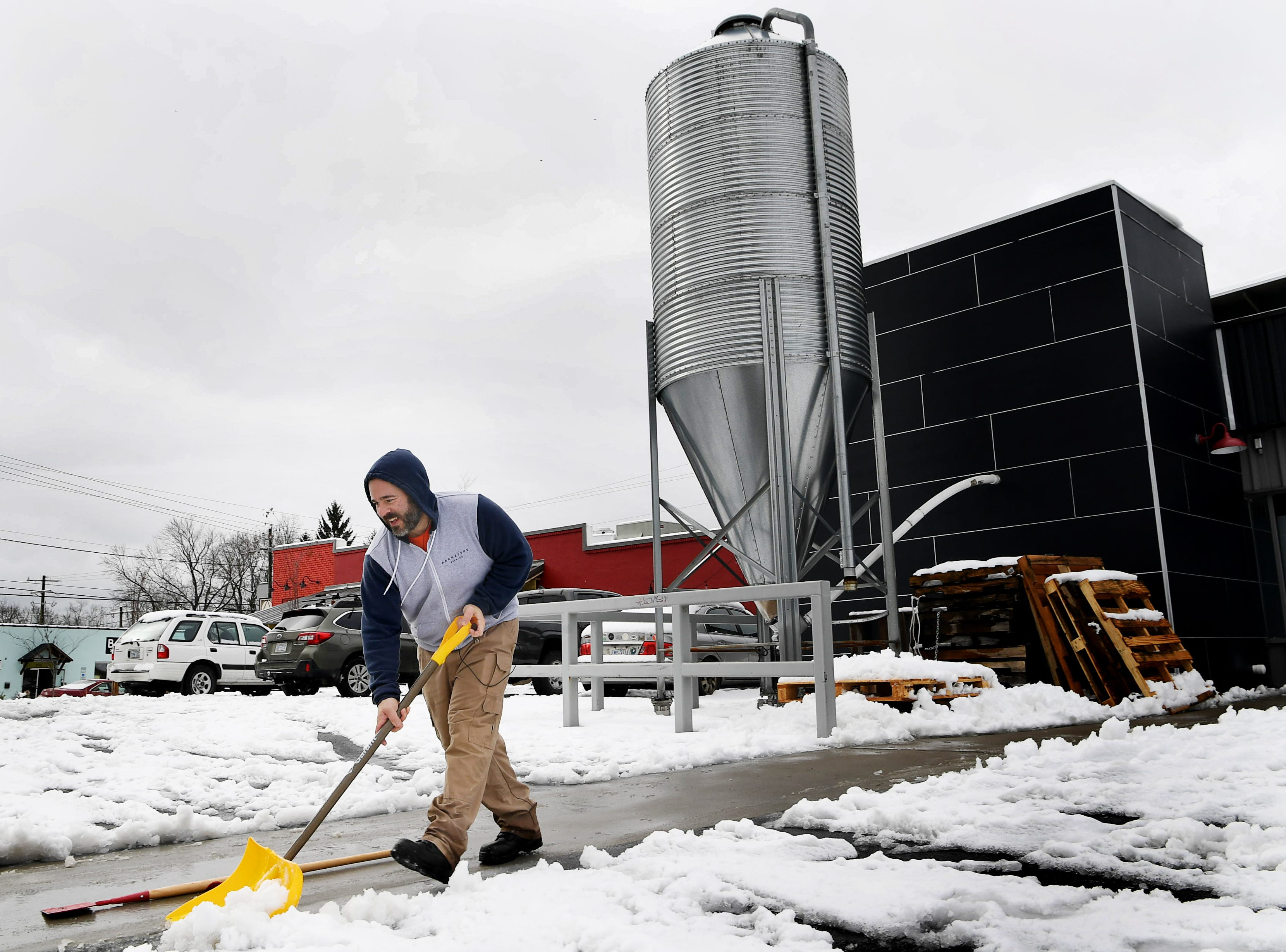 "Brad Casanova, co-owner of Archetype Brewing in West Asheville, clears a walkway Dec. 10 in front of his business, which stayed open through the snowstorm. ""The people who could walk here appreciated that we were open,"" said Casanova."