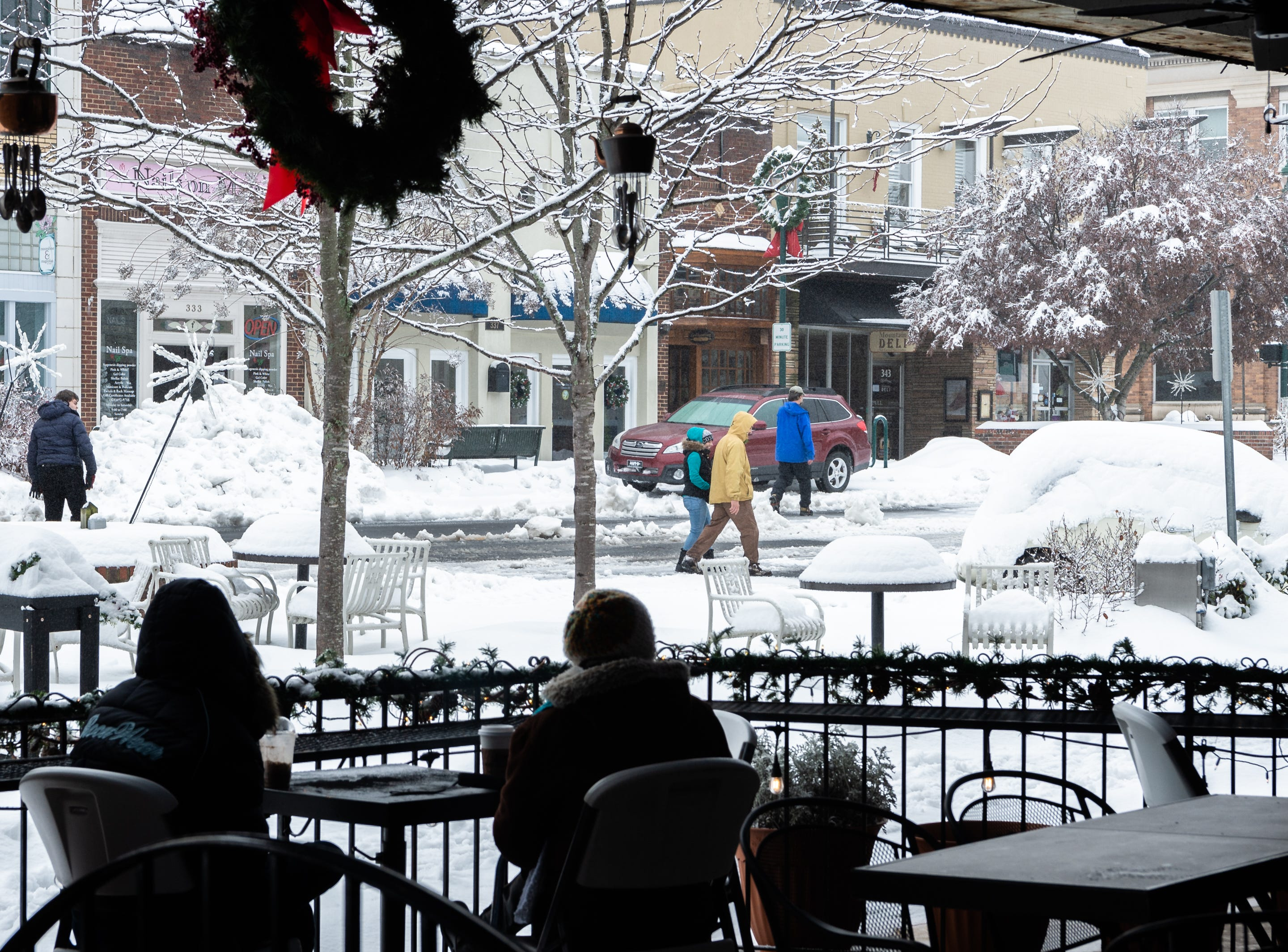 Patrons sit on the patio at Black Bear Coffee Co. as pedestrians walk down Main Street in Hendersonville Dec. 9, 2018.