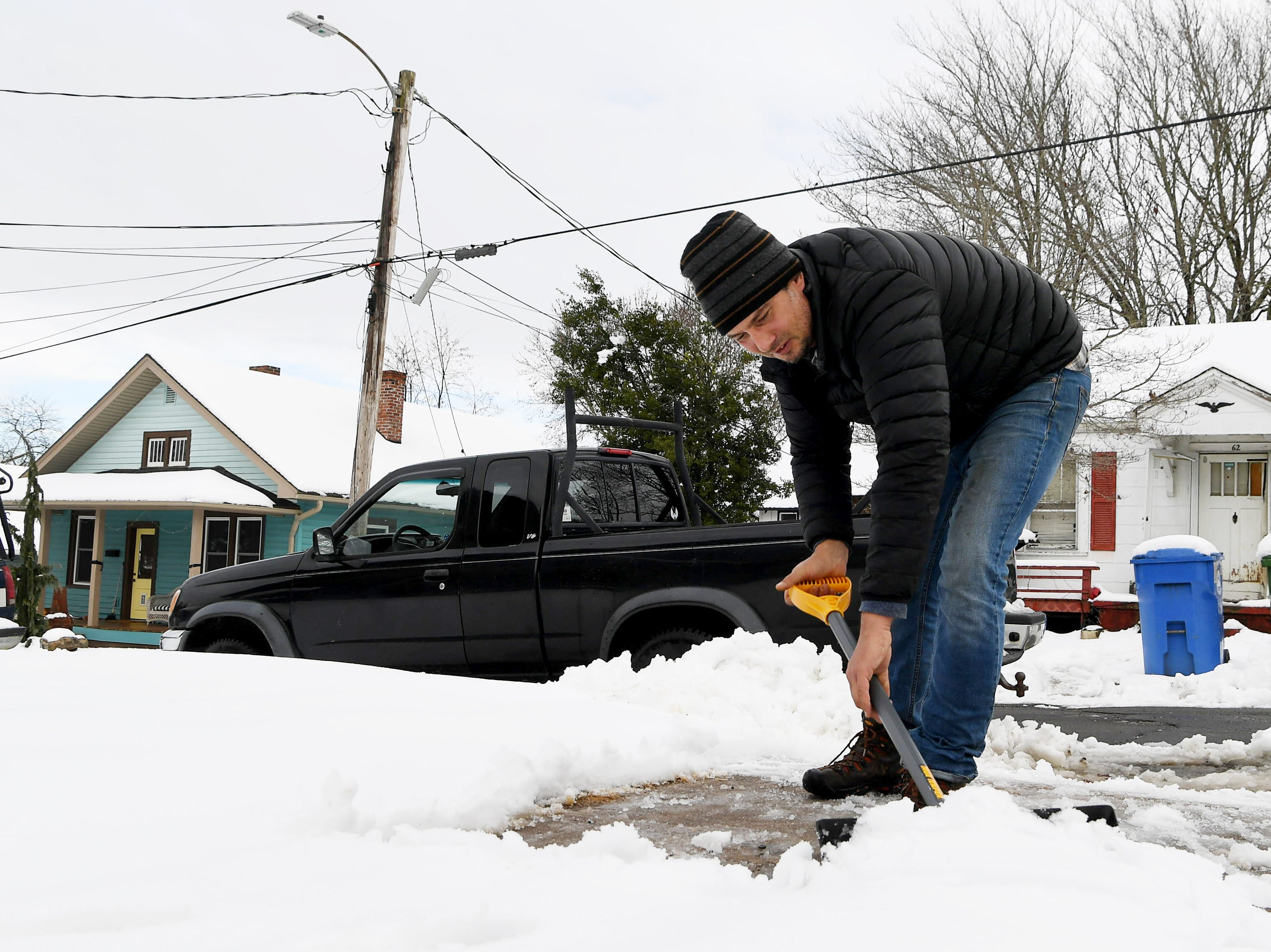 "Jared Woolsey shovels his neighbor's driveway Dec. 9, 2018 after Asheville was blanketed with 11 inches of heavy snow. ""I was excited for the snowstorm,"" said Woolsey, ""it was an opportunity to hang out with my son and do a little sledding."""