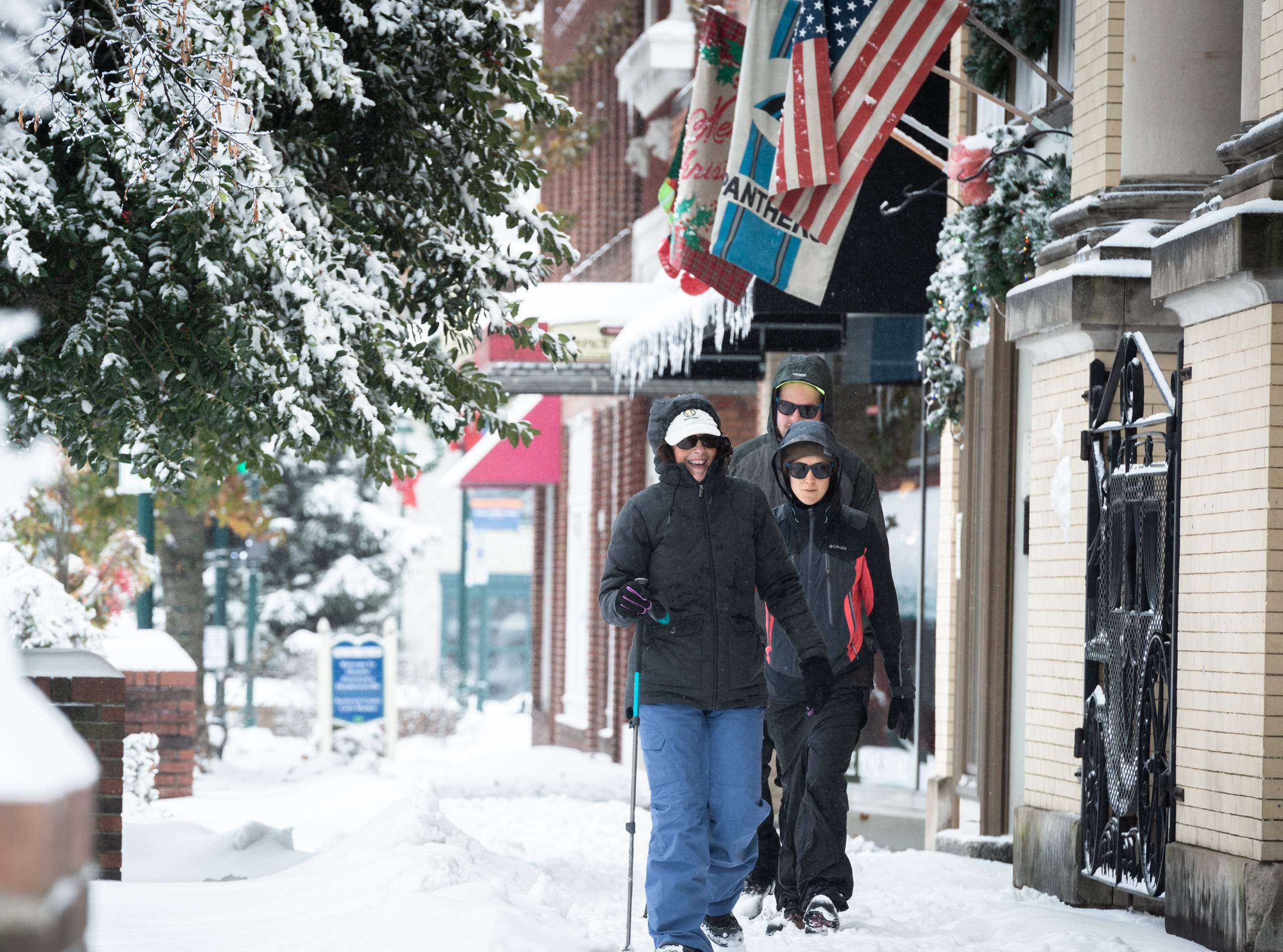 Elaine Anderson, Alana Anderson and Chad Anderson, all all down Main Street in Hendersonville after a night of heavy snowfall, accumulating 10-11 inches Dec. 9, 2018. At 5 p.m there were nearly 9,600 power outages.