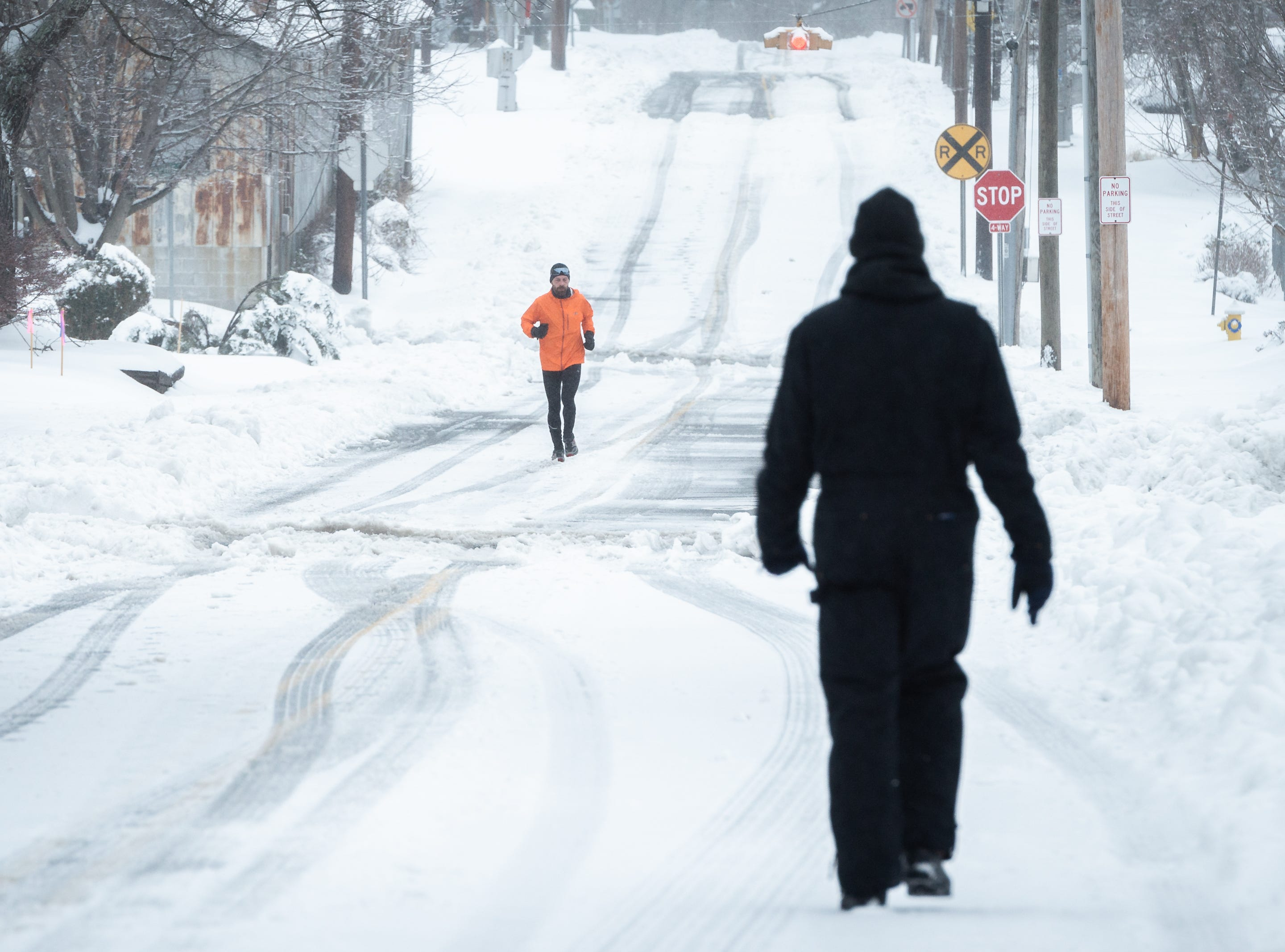A runner and a pedestrian in downtown Hendersonville after a night of heavy snowfall, accumulating 10-11 inches Dec. 9, 2018. At 5 p.m there were nearly 9,600 power outages.