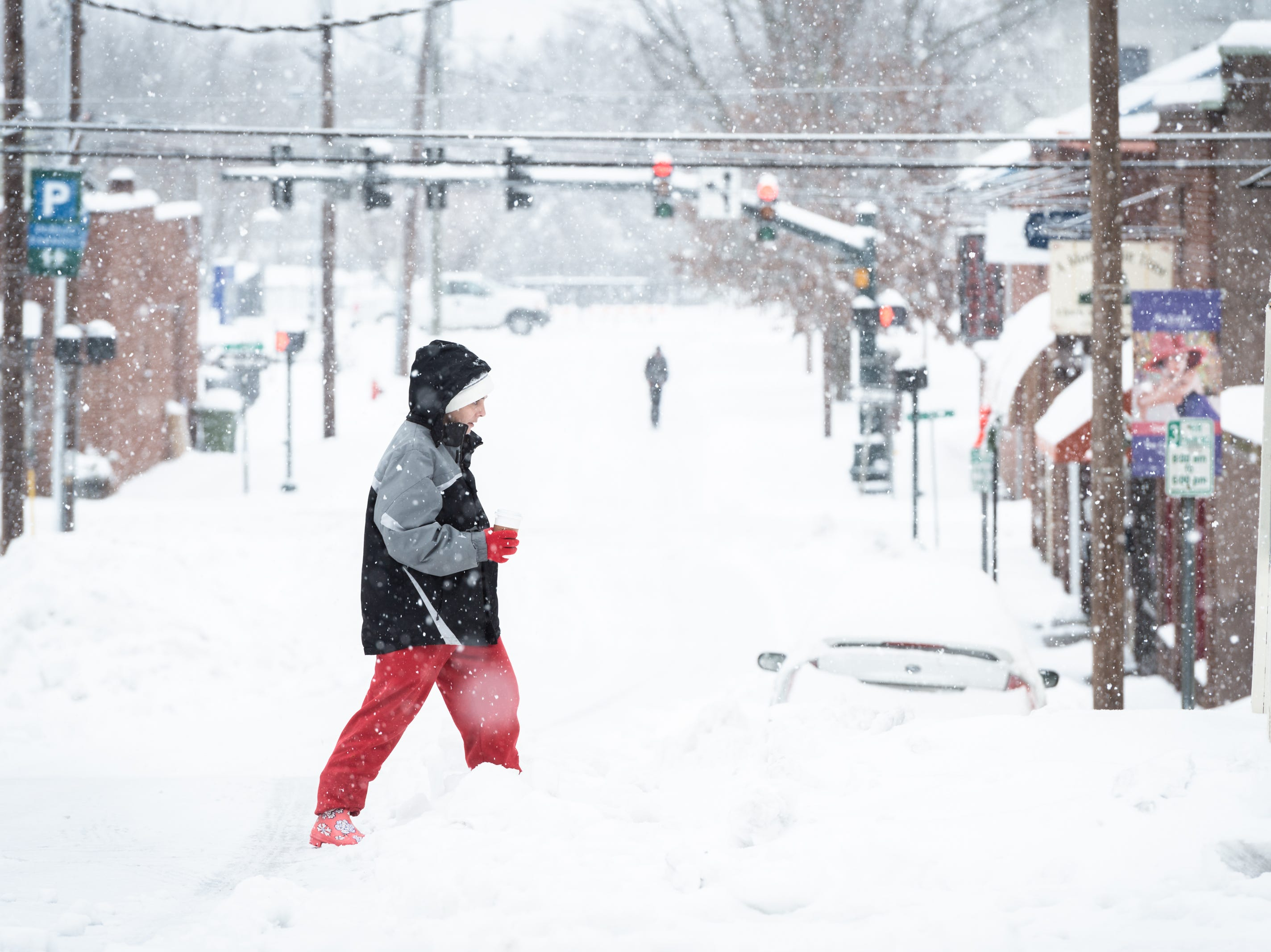 A pedestrian strolls down Main Street in Hendersonville after a night of heavy snowfall, accumulating 10-11 inches Dec. 9, 2018. At 5 p.m there were nearly 9,600 power outages.