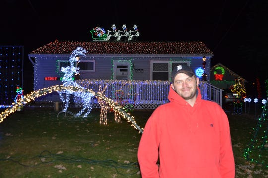 Andrew Logan in front of his decorated house at 936 Belton Ave. in Battle Creek.