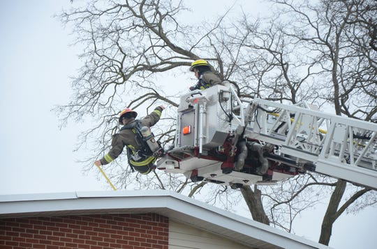 A firefighter falls from the ladder truck platform as he climbs on the roof to fight a fire at a Springfield home Monday, Dec. 10, 2018. He was not injured.