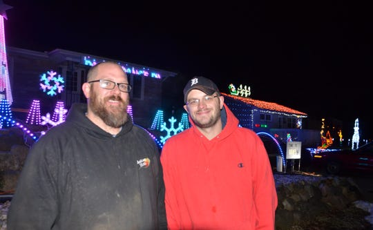 Neighbors Erik Wawzysko (L) and Andrew Logan stand in front of their decorated houses. The two wagered a case of beer on who could do the best Christmas decorations.