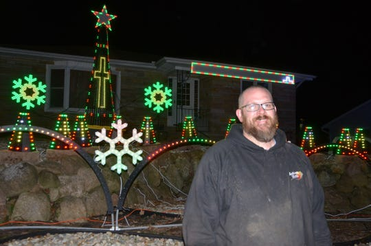 Erik Wawzysko in front of his decorated house at 942 Belton Ave. in Battle Creek.