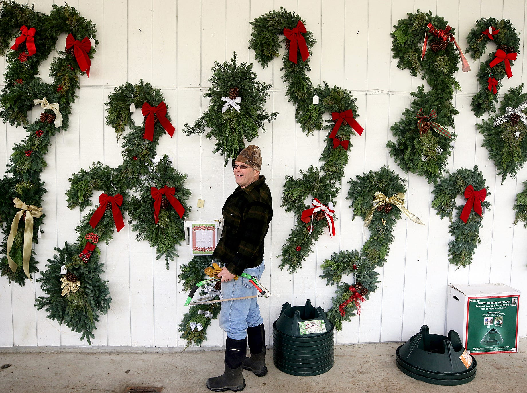 Dr. James Little of the All Creatures Animal Hospital in Gorst chooses hand made wreathes at the Bacon's Christmas Tree Farm on West Belfair Valley Rd, between Bremerton and Belfair on Monday, December, 10, 2018. He was getting the wreaths for his office Christmas party and to send some to family back east. The tree farm is closing early this year as Monday was the last day.