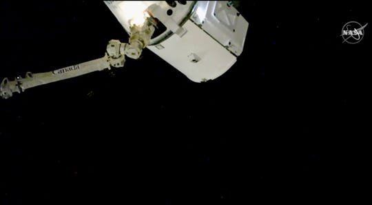 In this image taken from NASA Television, the SpaceX Dragon cargo spacecraft is captured by a robotic arm for docking to the International Space Station, Saturday, Dec. 8, 2018. A SpaceX delivery full of  Christmas goodies has arrived at the International Space Station. The Dragon capsule pulled up at the orbiting lab Saturday, three days after launching from Florida. (NASA TV via AP)