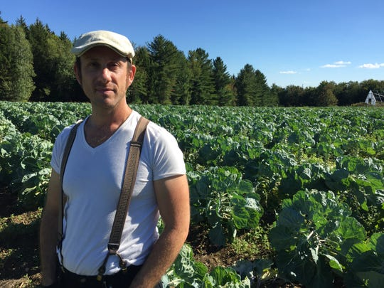 "Kris Gruen, shown standing among Brussels sprouts on his family's farm in Worcester, said he learned in his youth that ""working with the earth is real."""