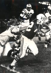 SEPTEMBER 23, 1972: Reading ball carrier Jim Sowder (22) heads around end with Wyoming defender Steve Streight (33) hanging on.