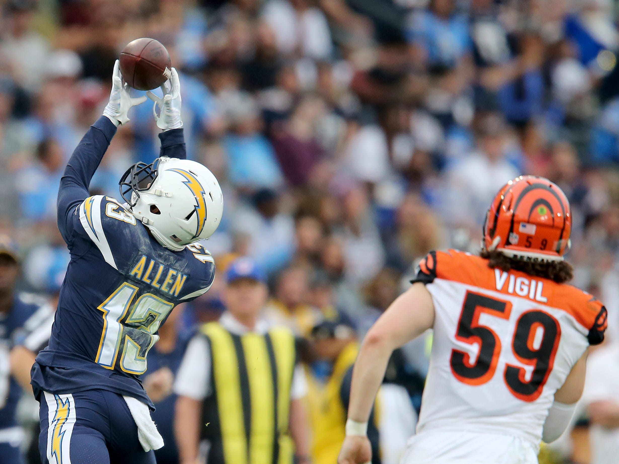 Los Angeles Chargers wide receiver Keenan Allen (13) completes a catch as Cincinnati Bengals outside linebacker Nick Vigil (59) gives chase in the fourth quarter of a Week 14 NFL football game, Sunday, Dec. 9, 2018, at StubHub Center in Carson, California.
