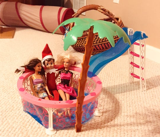 Elf on the Shelf gets a little cuddle in a puddle with a Barbie on either side.