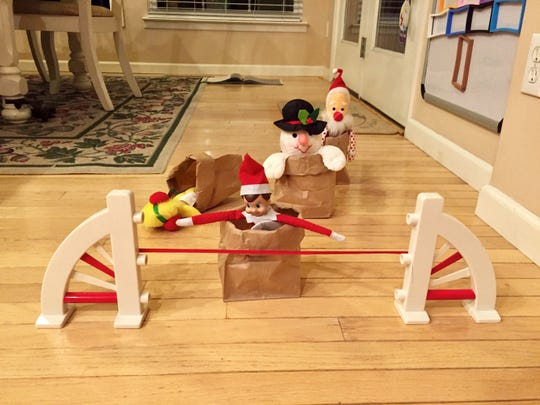 No looking back for Jack in a sack. Ken Kern's elf takes the lead in a sack race against Woodstock, Frosty and Santa.