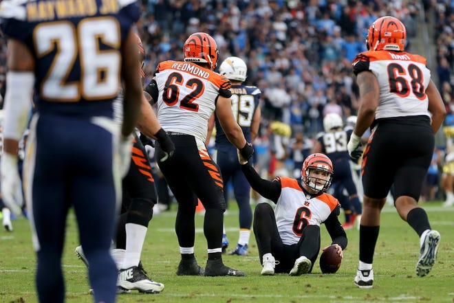 Cincinnati Bengals quarterback Jeff Driskel (6) is helped up by Cincinnati Bengals offensive guard Alex Redmond (62) after he is sacked on a two-point conversion play in the fourth quarter of a Week 14 NFL football game against the Los Angeles Chargers, Sunday, Dec. 9, 2018, at StubHub Center in Carson, California.
