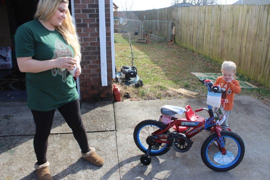 Jessica Philips watches as her 2-year old son Wyatt reacts to the bike that's now paid off, thanks to the kindness of a local couple who paid off all the layaway accounts at the Wal-Mart on Fort Campbell Boulevard.