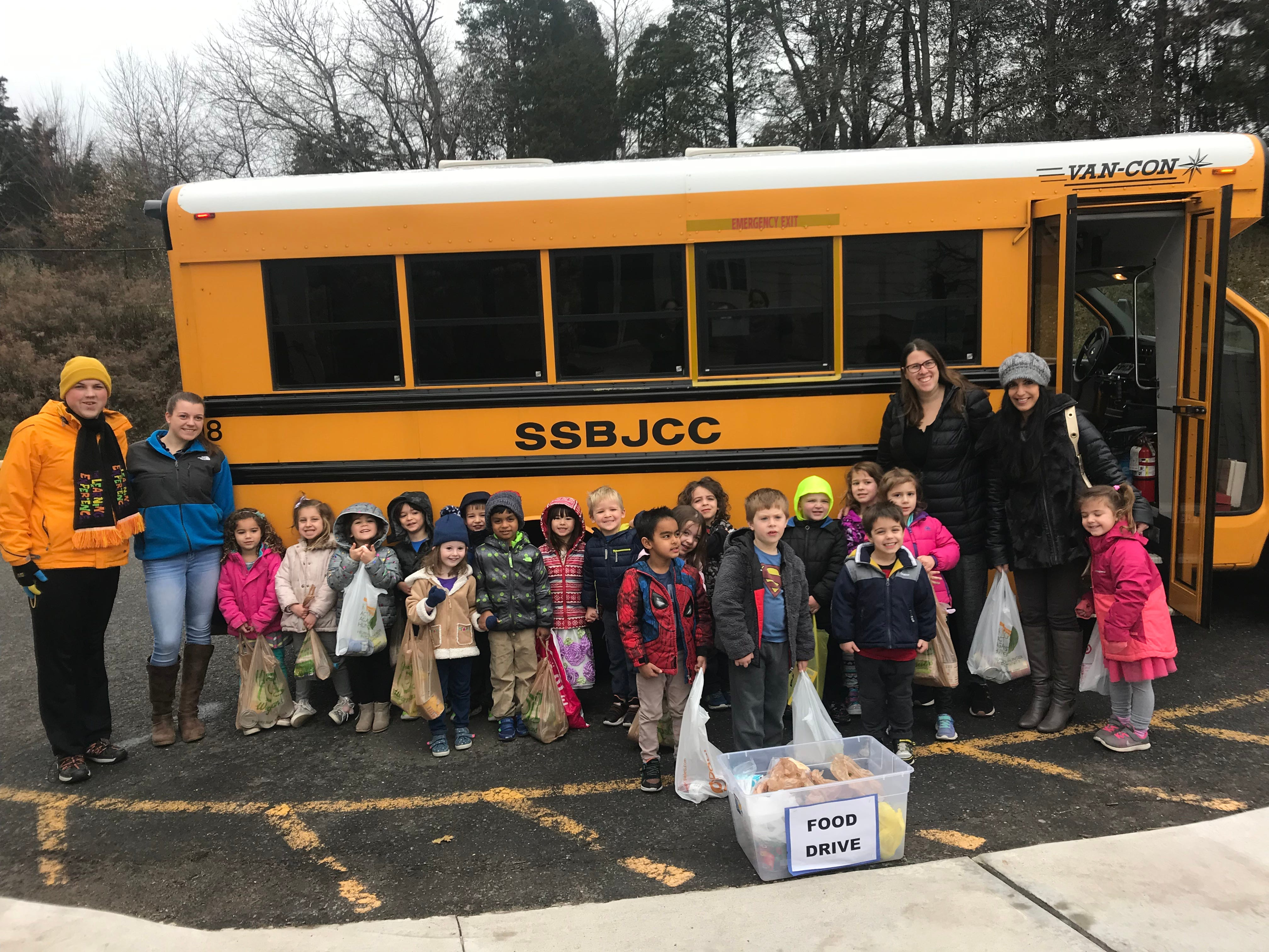 Pictured with bags of collected food are the children in the JCC Blaustein Early Childhood Center four-year-old class along with [left to right]: JCares Intern William Mahon, teacher Sam Ballow, teacher Marisa Berman and parent Sari Greaves.