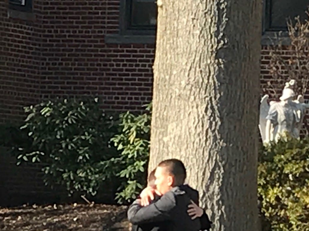 Two mourners hug following the funeral for Michael Sot, 20, of Clark.