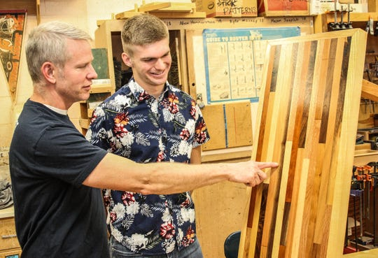 A table that Randal Henderson (left) made from scrap lumber is admired by Del Val senior Jake Norgard.