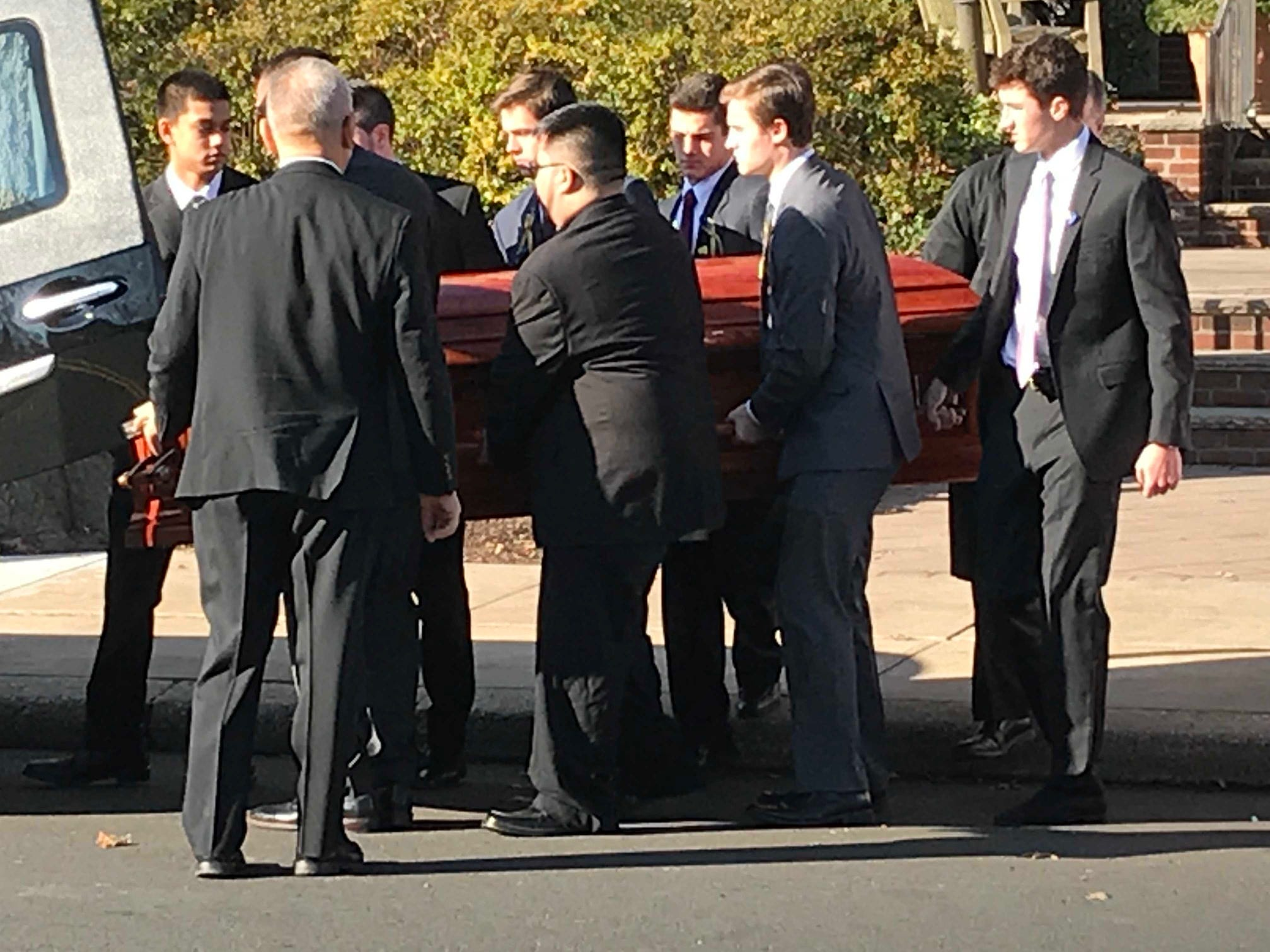 The coffin carrying Michael Sot is placed into the waiting hearse following his funeral.