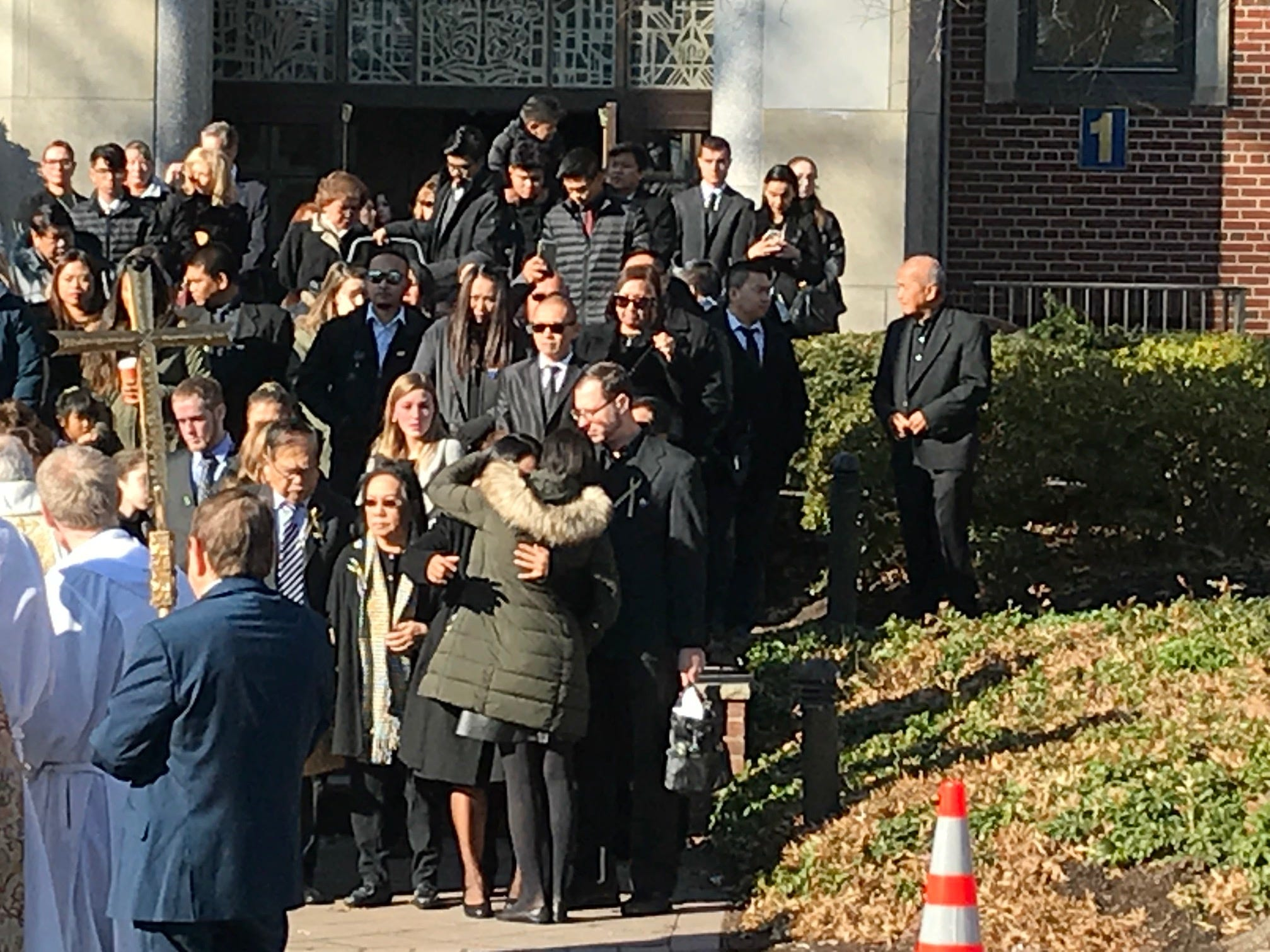 Family members hug following the funeral for Michael Sot, 20, of Clark.