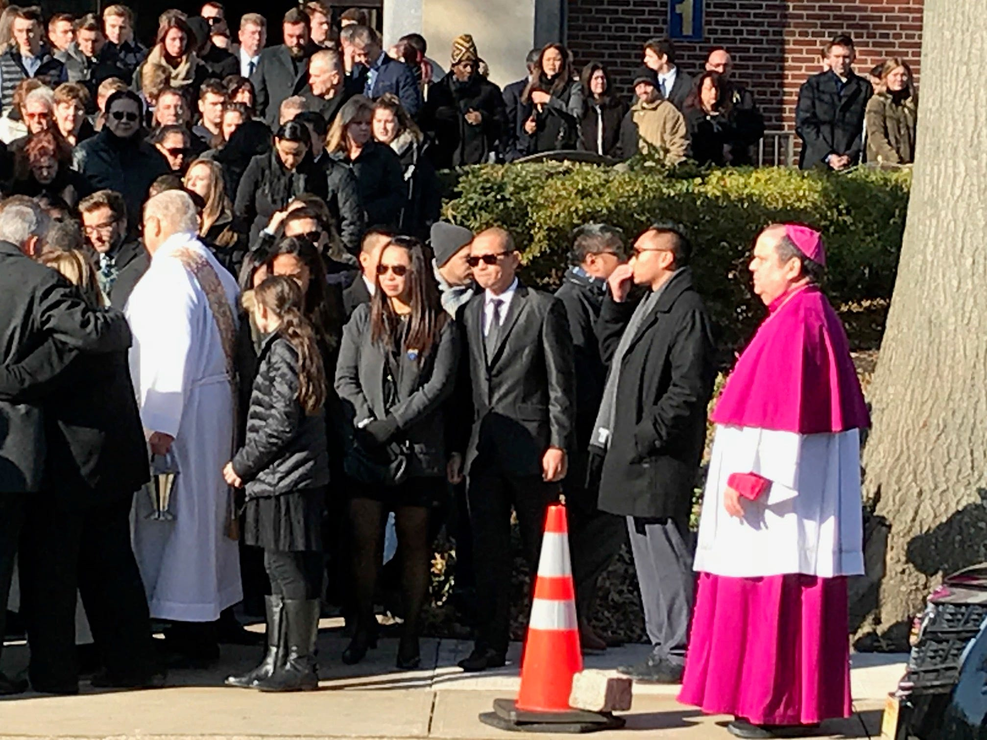 Michael Sot's family and friends gather outside the church following his funeral.