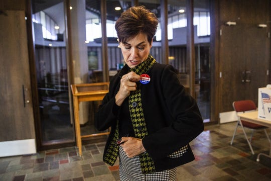 "Iowa Governor Kim Reynolds puts on a ""I voted"" sticker after casting her vote in the 2018 election on Tuesday morning, Nov. 6, 2018, in her hometown of Osceola."