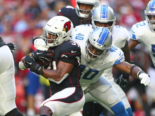 Arizona Cardinals running back David Johnson is tackled by Detroit Lions linebacker Jarrad Davis in the first half at State Farm Stadium, Dec. 9, 2018.