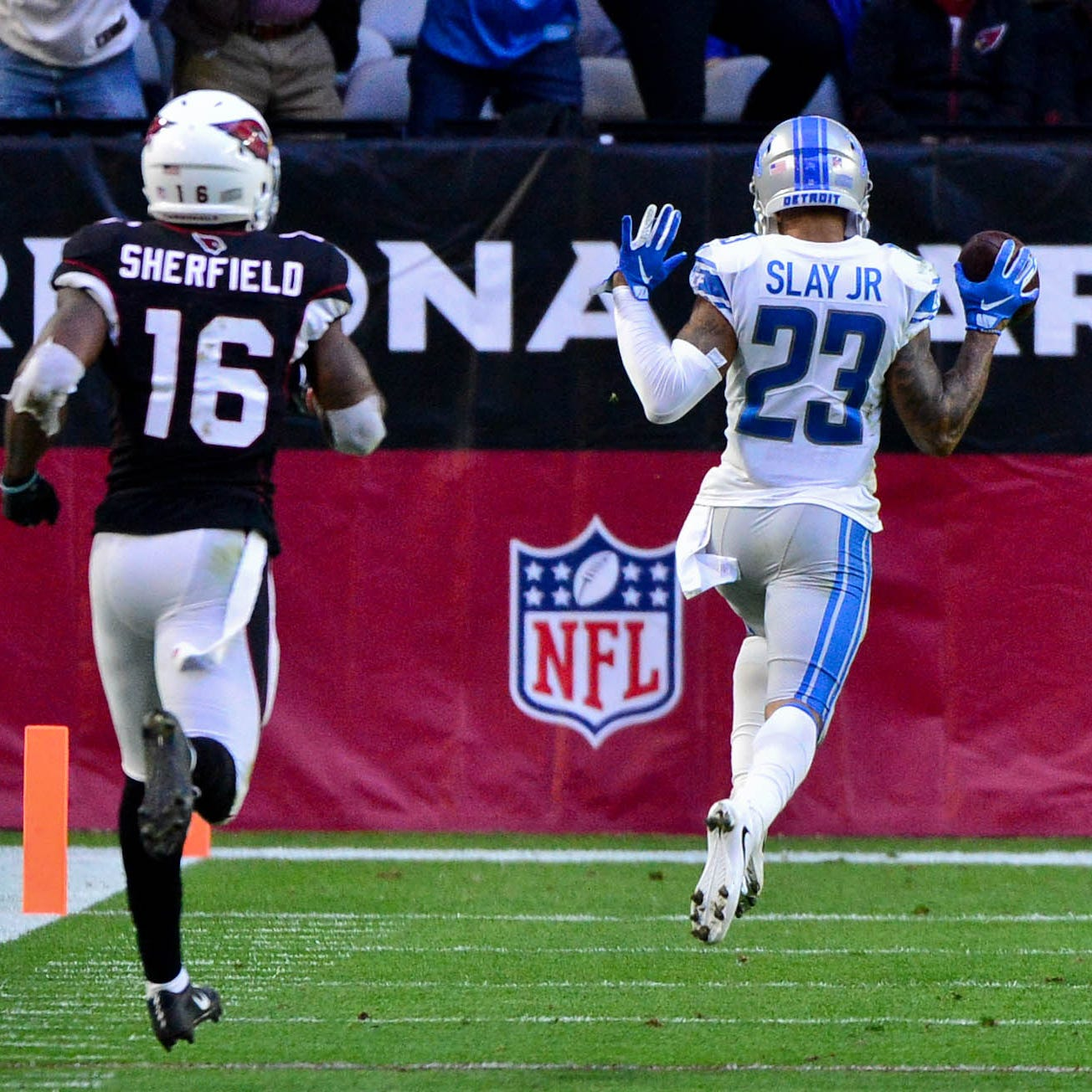 Detroit Lions cornerback Darius Slay returns an interception for a touchdown as Arizona Cardinals receiver Trent Sherfield watches during the second half at State Farm Stadium, Dec. 9, 2018.