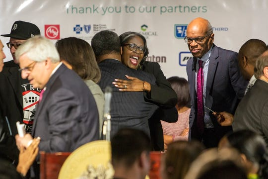 Alicia George of Motor City Java reacts after she, Mayor Duggan and corporate executives announce historic, multi-million dollar commitment to Detroit neighborhoods, in Detroit, Mich., Monday, Dec, 10, 2018