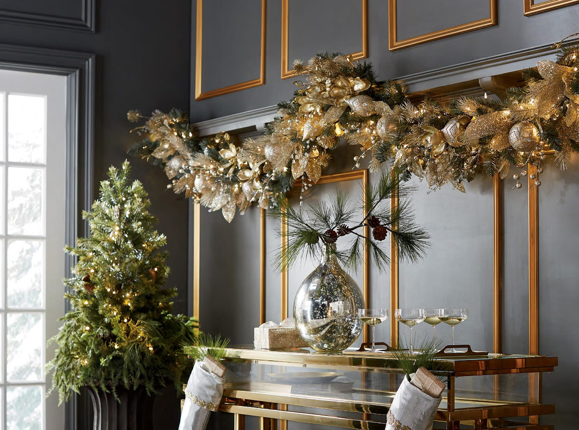 : A thick garland from Frontgate is made up of faux greens, ornaments, crystals, gold metallic ribbons and gold-edged forest green ribbons that lend opulence. The Gilded Elegance garland lavishly draws the eye above a brass console in a room punctuated with gold picture moldings.