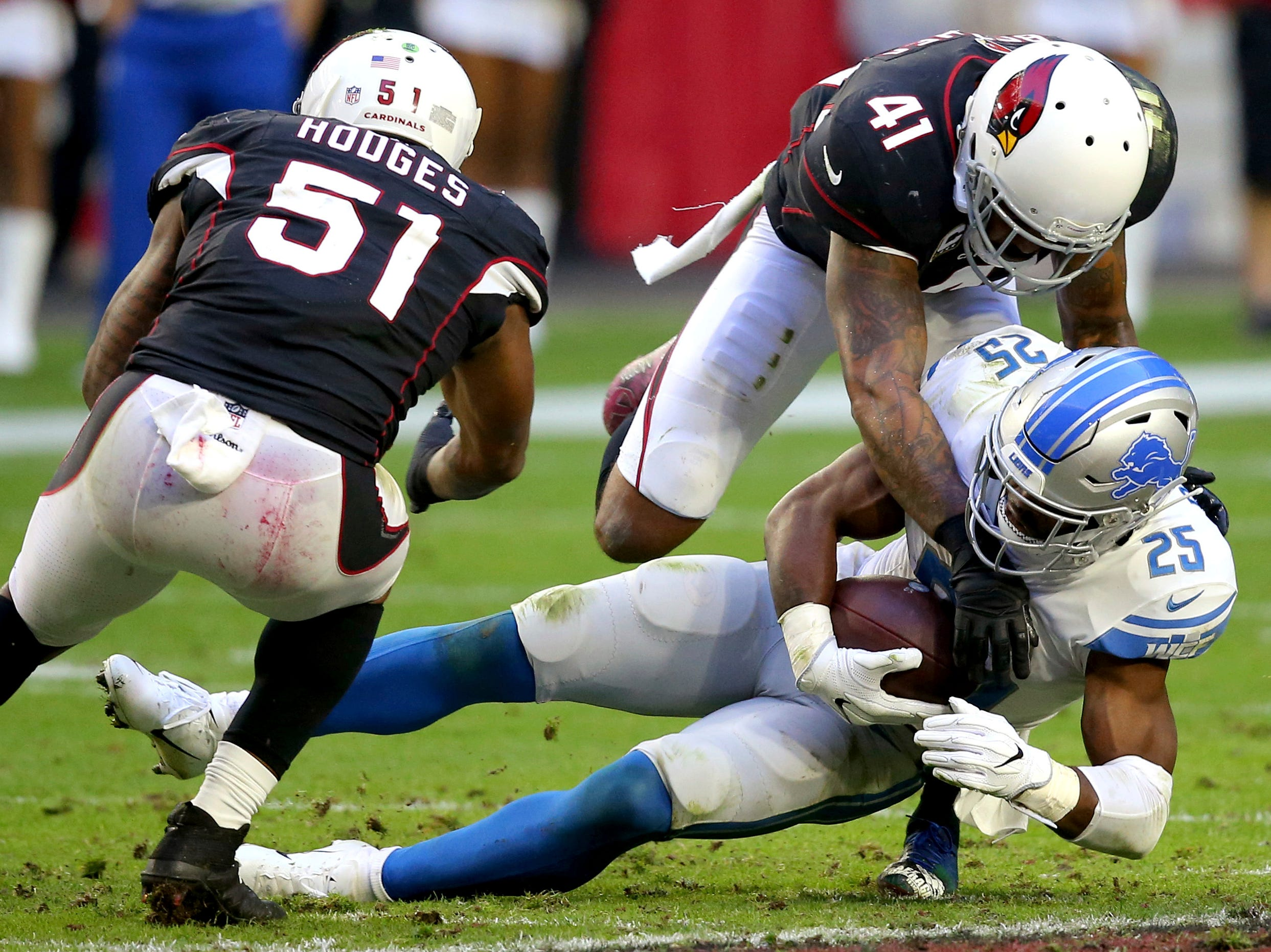Detroit Lions running back Theo Riddick (25) is hit by Arizona Cardinals free safety Antoine Bethea (41) as linebacker Gerald Hodges (51) pursues during the second half.