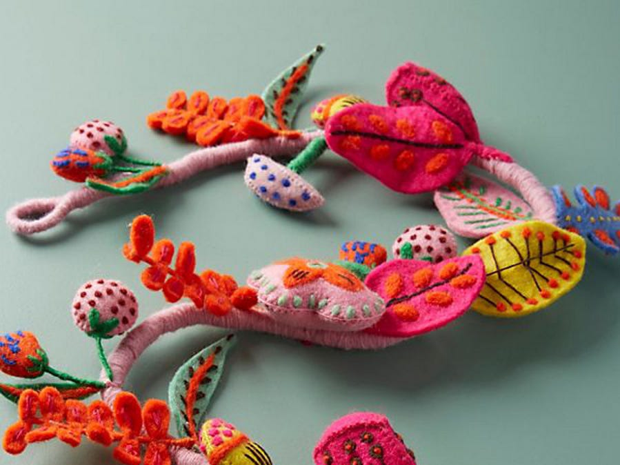 Colorful leaves and berries with hand-sewn contrast stitching fashion a charming hand-crafted garland of felt at Anthropologie.