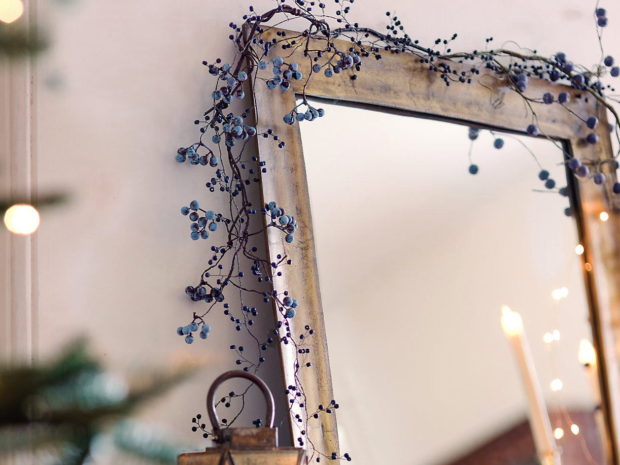 Blueberries are an unexpected embellishment in a delicate spray from Terrain, wrapping around a mirror washed in gold and silver.