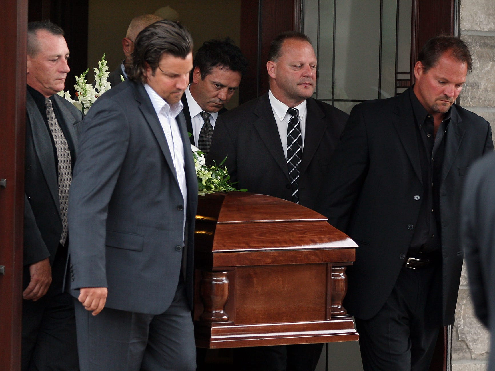 Pallbearers Joey Kocur, right, Gerry Gallant and Doug Gilmore, behind right, and others, carry the casket of Bob Probert from Families First Funeral Home to Windsor Christian Fellowship for a funeral service for one of the toughest players in NHL history.
