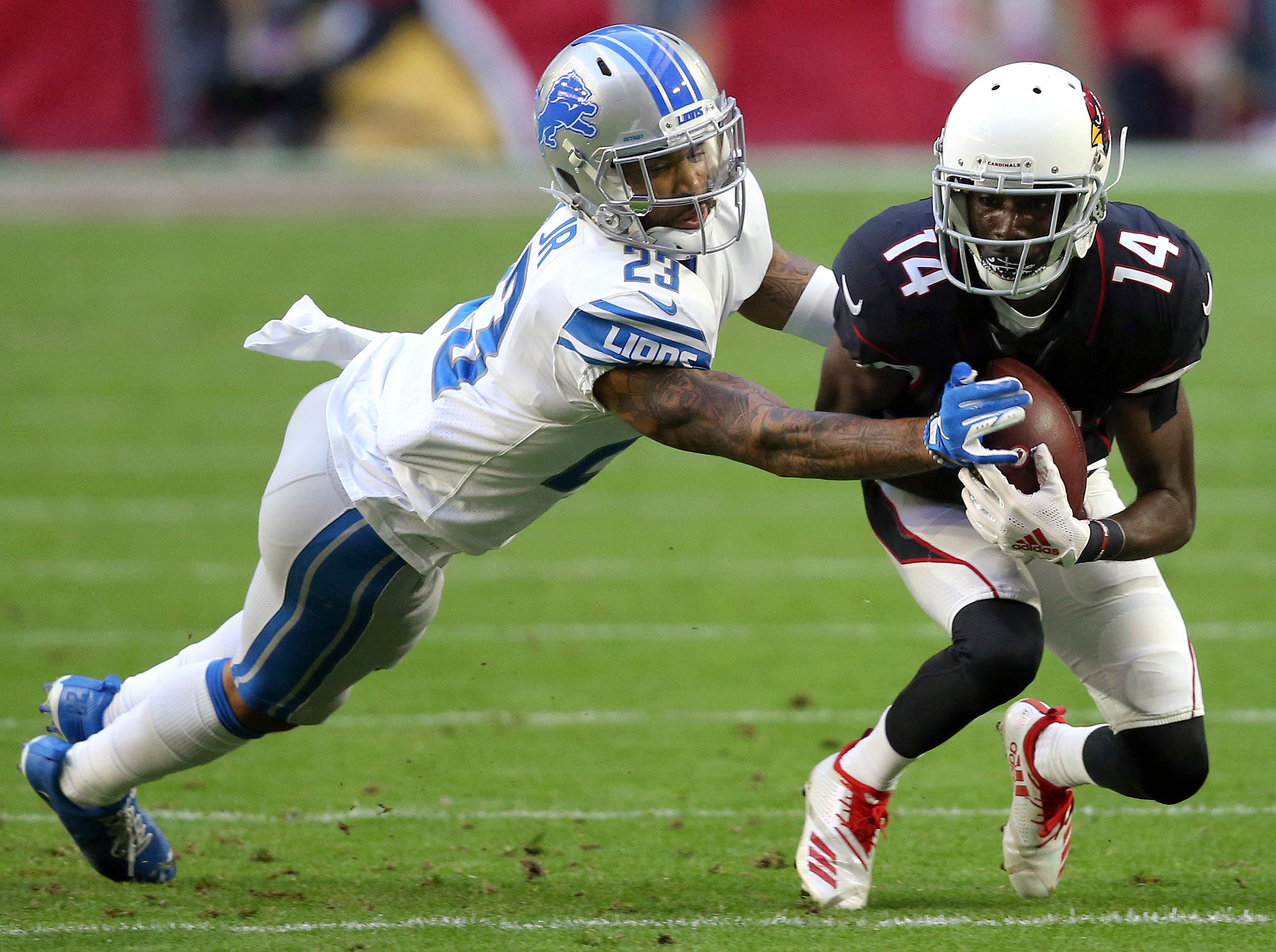 Arizona Cardinals wide receiver J.J. Nelson (14) pulls in a pass as Detroit Lions cornerback Darius Slay (23) defends during the first half.