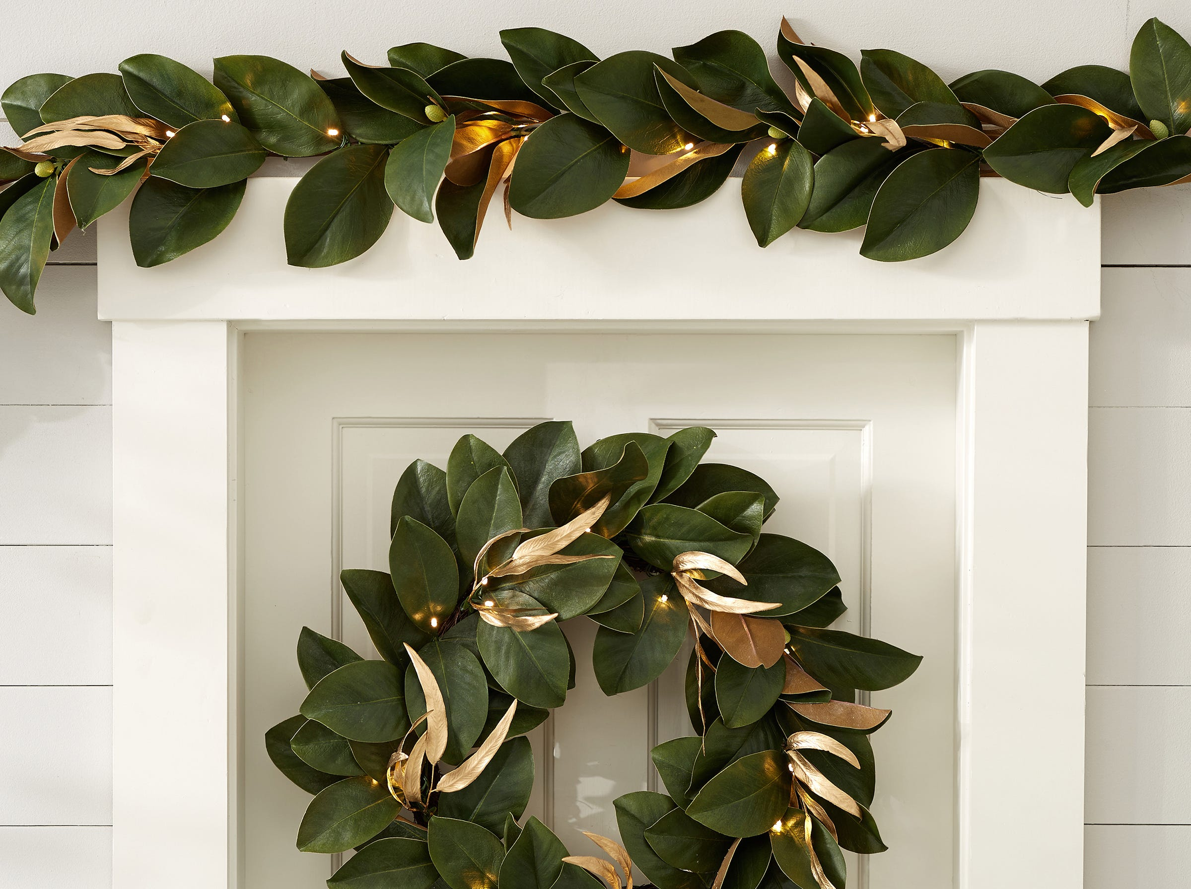 Classic shiny magnolia leaves, with their familiar rich dark green and copper leaves are lit with 25 LED lights on a 5-foot garland (or 35 lights on the 8-foot option). The garland and matching wreath, which have on/off switches on a battery box, are from Pottery Barn. They are a handsome tandem crowning the door frame and on the door.