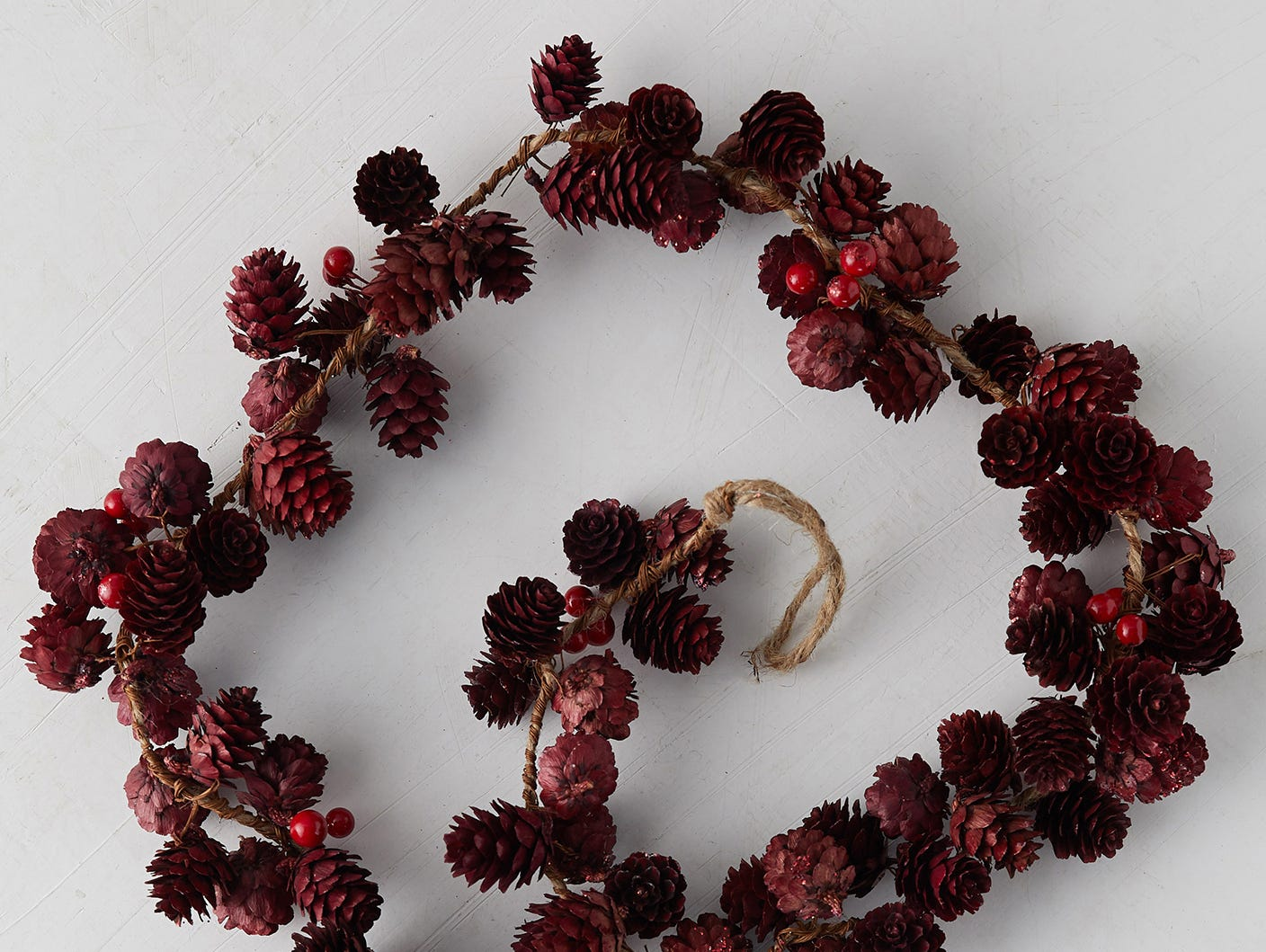 Pine cones in shades of garnet, punctuated with red berries, add nuanced color and texture wherever you choose to place this garland from Anthropologie.