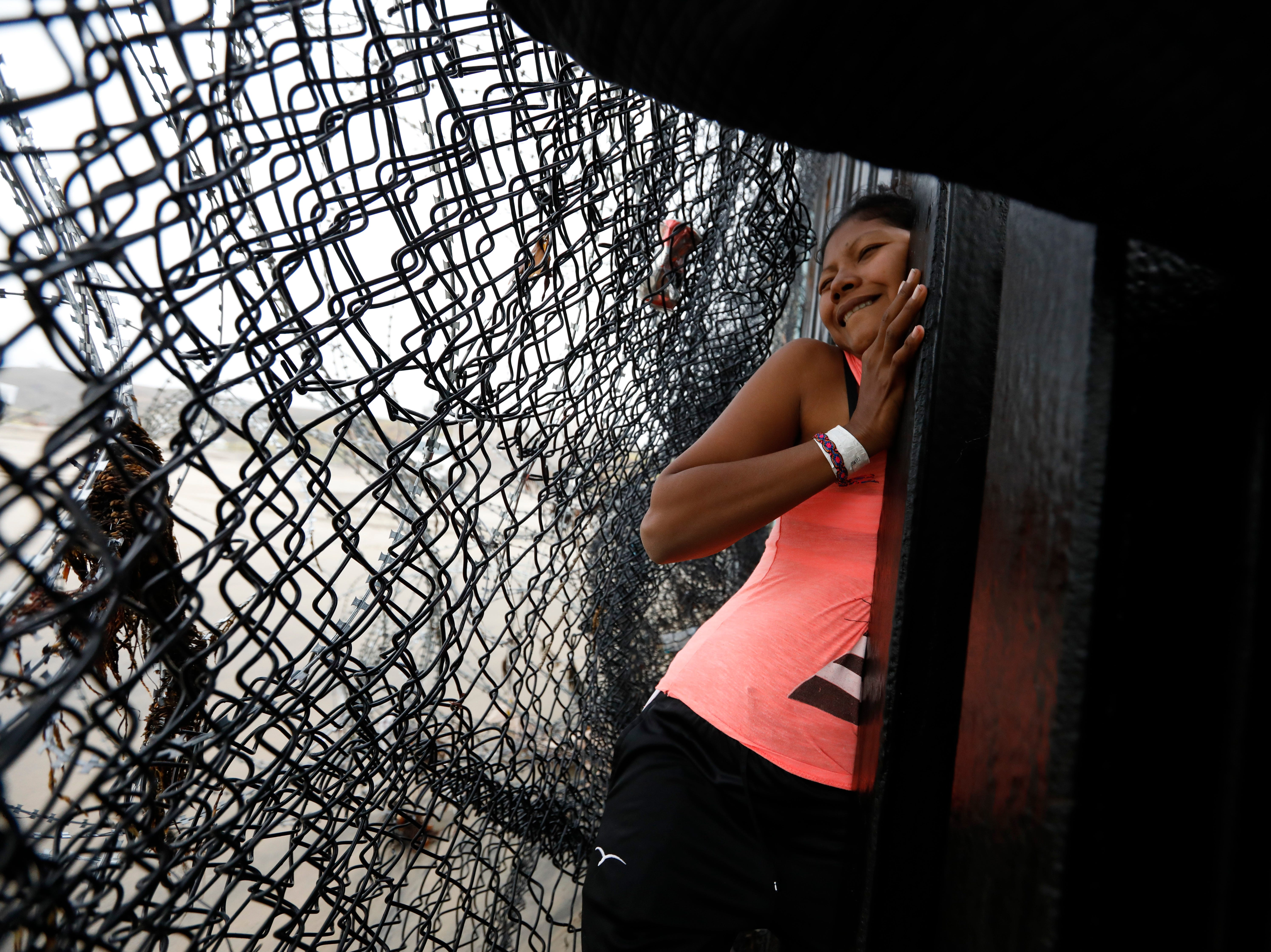 A Honduran migrant, followed by her daughter, squeezes through a gap in the U.S. border wall from Tijuana, Mexico, onto U.S. soil near Imperial Beach, Calif., Sunday, Dec. 9, 2018. Discouraged by the long wait to apply for asylum through official ports of entry, many Central American migrants from recent caravans are choosing to cross the U.S. border wall illegally and hand themselves in to Border Patrol agents to request asylum.