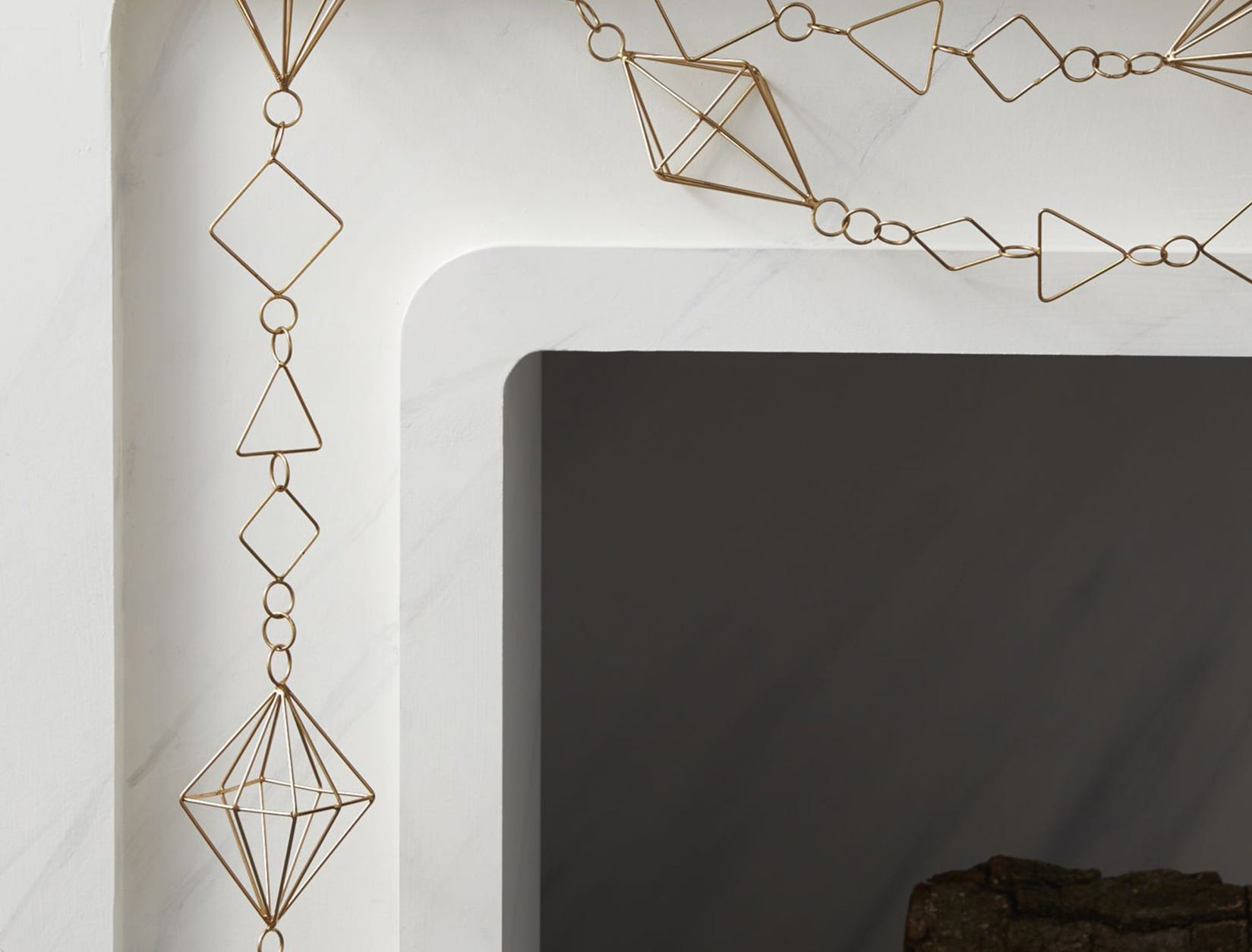 A series of geometric shapes in different sizes create a fancy chain that looks like a necklace -- simple and modern on a white marble mantel. The garland is from CB2.