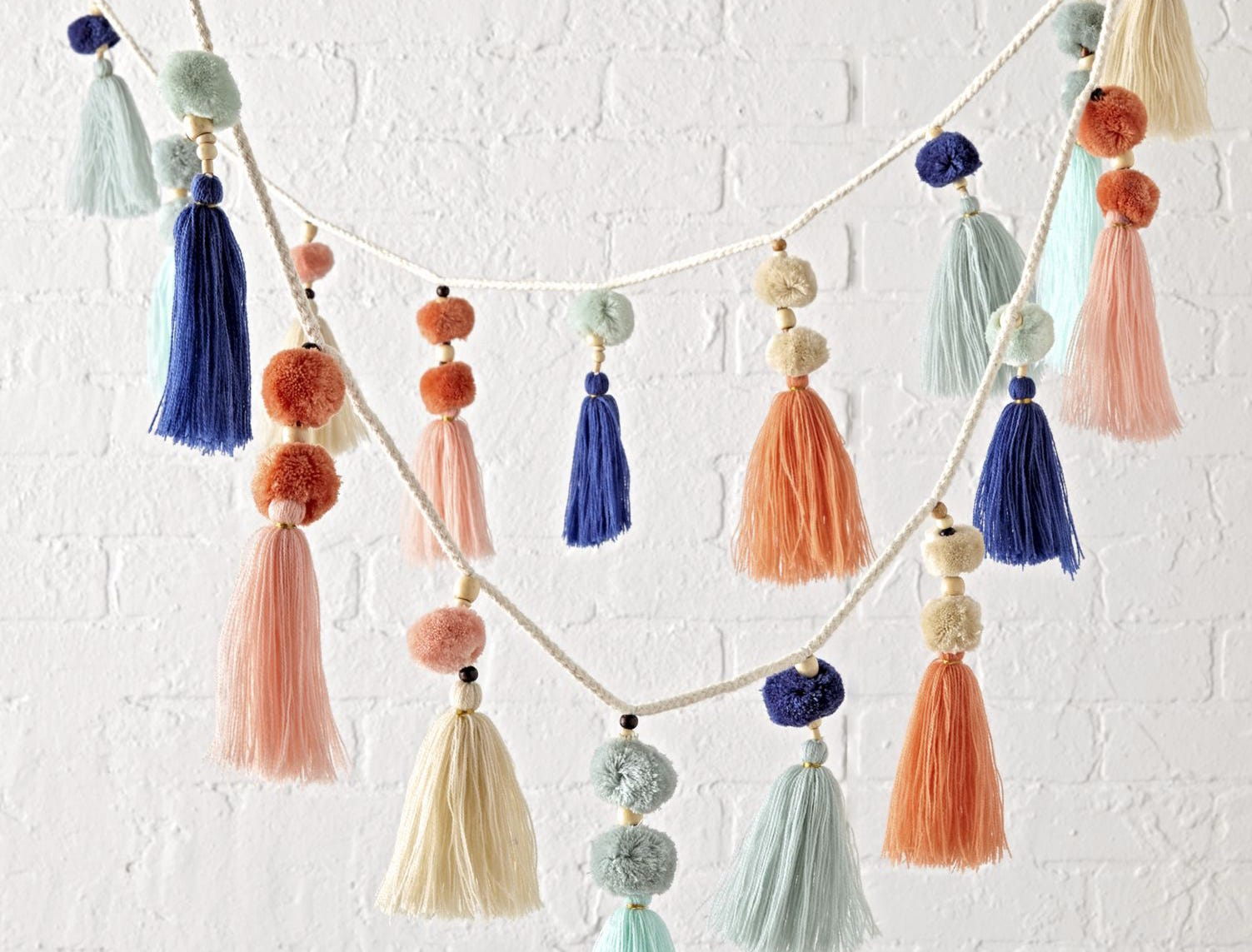 """Playful tassels and pompoms in peachy pastels, teamed with pale to deep blue are """"like a party for your decor,"""" says Crate and Barrel."""